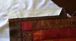 7. Sew short border pieces to dark strips as if they were another strip