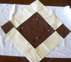 Center square on foundation fabric with first set of strips laid out.