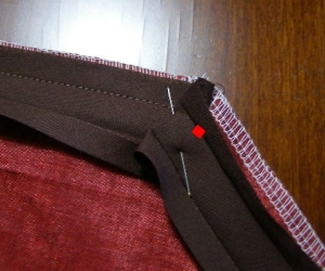 88.  Fold bias binding up and then down to form a small pleat.  Pin.  Sew from red dot.