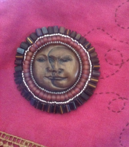 Face Cabochon secured to linen jacket.