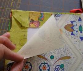 Corners of fabric are trimmed away, glued down and covered with decorative paper.