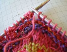 Turn so 5 loops are on left needle and purl those five loops.