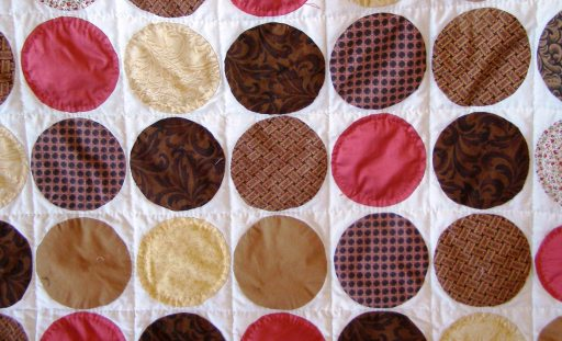 CIrcles appliqued on.  Hand quilted along grid lines.