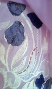 Embellishment on vertical lace piece.